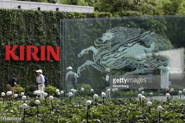 Visitors stand near the Kirin Holdings Co. Logo displayed at a Kirin Brewery Co. Factory in Yokohama, Japan, on Tuesday, June 11, 2019. Heineken...