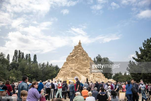 Visitors stand near the Sandburg sandcastle on September 1 2017 in Duisburg Germany A local travel agency commissioned the building of the sandcastle...