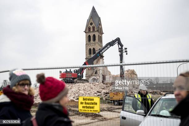 Visitors stand nearby as an excavator demolishes Saint Lambertus church following protests by activists on January 9 2018 in Immerath Germany The...