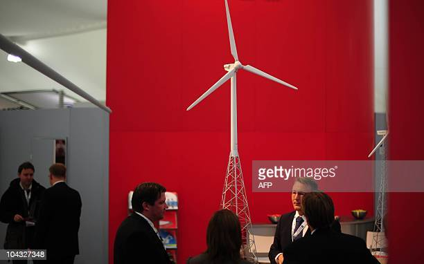 Visitors stand next to a model of a wind turbine at the Wind Energy 2010 fair on September 21 2010 in Husum northern Germany The fair for Wind Energy...