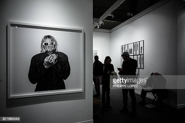 Visitors stand next to a photograph of late US singer Kurt Cobain by Dutch photographer Anton Corbijn during the opening of the 20th edition of Paris...