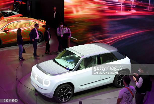 Visitors stand next to an IQ LIFE car at the booth of German carmaker Volkswagen at the International Motor Show Germany, on September 8, 2021 in...