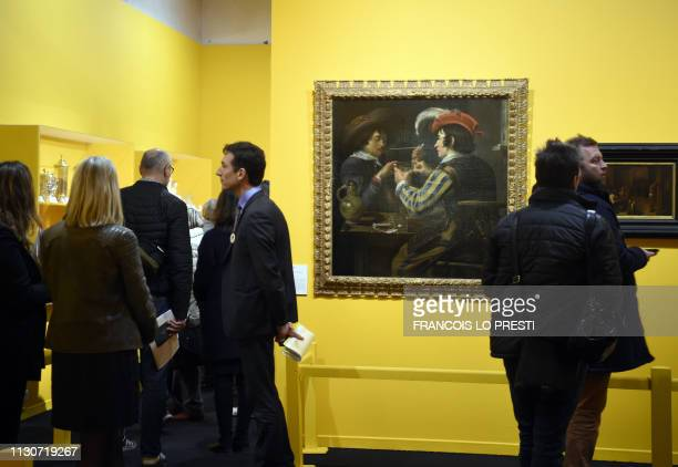 Visitors stand next to the painting 'The Card Players' by Flemish painter Theodore Rombouts during the preview of the exhibition 'A boire Quand la...