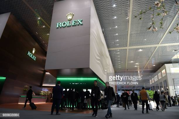 Visitors stand next to the stand of Swiss watchmaker Rolex during press day on March 21 on the eve of the opening of the Baselworld watch and...