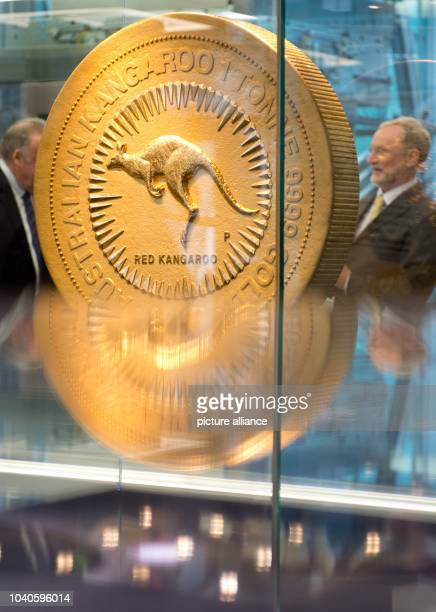 Visitors stand next to the world's biggest gold coin at the Baden-Wuerttembergische Bank in Stuttgart, Germany, 29 January 2014. The coin has a...