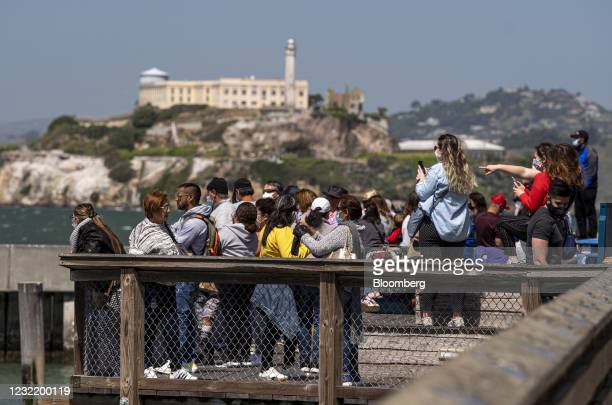 Visitors stand on Pier 39 in front of Alcatraz Island in San Francisco, California, U.S., on Thursday, April 8, 2021. California officials plan to...