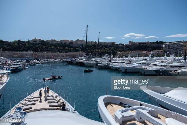 Visitors stand on the bow deck area of luxury superyacht Metis manufactured by Azimut Bentti SpA left as sits moored with other vessels during the...