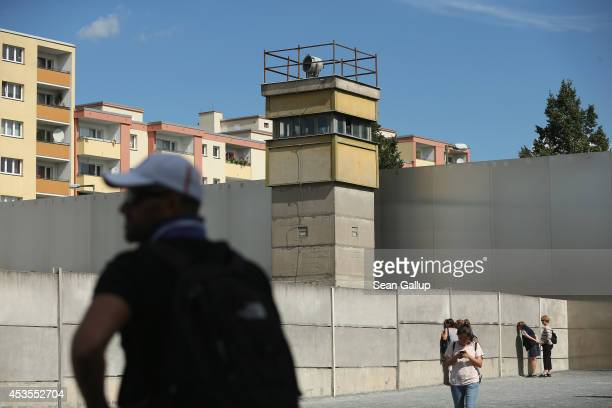 Visitors stand on the former east side at the inner structure of the former Berlin Wall on the 53rd anniversary of the construction of the Wall at...