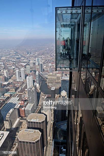 Visitors stand on the glass balcony at the skydeck of the Willis Tower in Chicago Illinois US on Wednesday Feb 13 2013 Willis Tower formerly named...