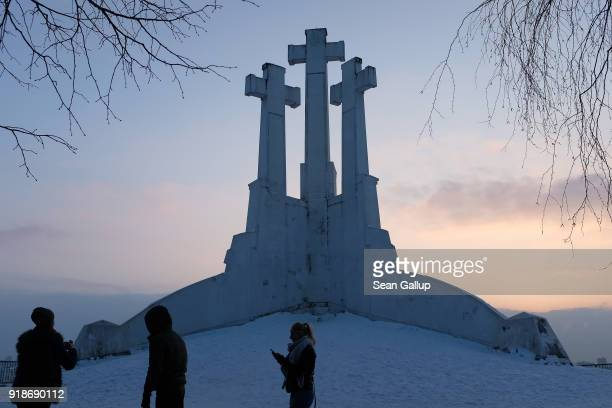 Visitors stand on the Hill of Three Crosses one of the city's major landmarks the day before the 100th anniversary of the restoration of Lithuanian...