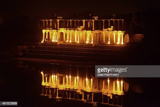 Visitors stand on the steps of 'Queens Palace' on the lake side of the ancient Sarkhej Roza Monument lit for the 'Sufi Festival' in Ahmedabad on late...