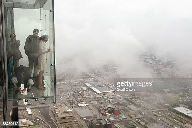 Visitors stand out on the Ledge a new glass cube that juts out from the 103rd floor Skydeck of the Sears Tower during a media preview July 1 2009 in...