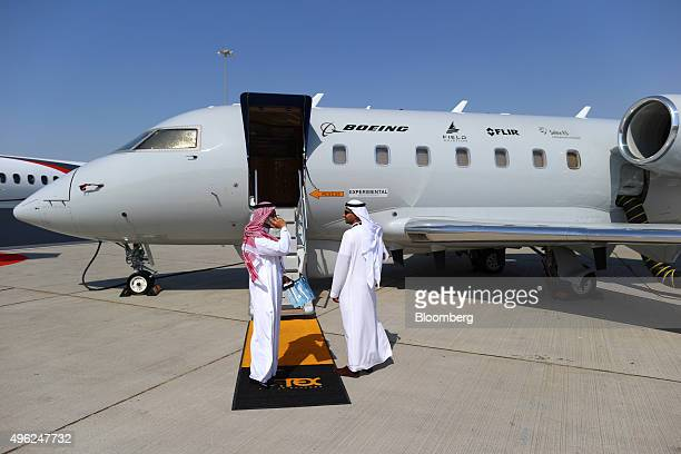 Visitors stand outside the entrance to a Bombardier Inc Challenger 604 jet used as a Boeing Co experimental aircraft on the opening day of the 14th...