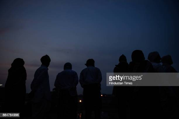 Visitors stand seen at Raj Ghat at dusk on a cold and smoggy day on December 3 2017 in New Delhi India Delhi witnessed a sharp drop in temperature in...
