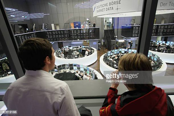 Visitors standing on a sightseeing platform watch the trading floor of Frankfurt stock exchange during a trading session on September 15 2008 in...
