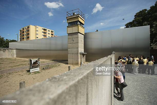 """Visitors standing on the former east side at the inner structure of the former Berlin Wall peek between the slits into the former """"death strip"""" on..."""