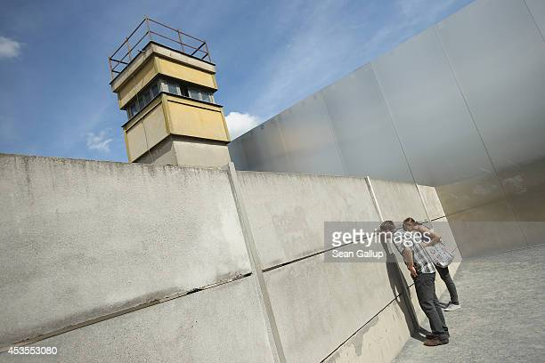 Visitors standing on the former east side at the inner structure of the former Berlin Wall peek between the slits on the 53rd anniversary of the...