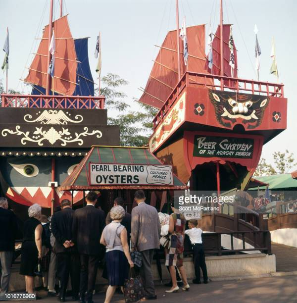 Tourists stop at a 'Pearl Bearing Oysters' display in front of the Beer Garden of the Hungry Dragon at the Hong Kong Pavilion at the World's Fair in...