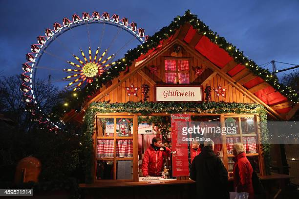 Visitors stop at a stall selling Gluehwein next to an illuminated ferris wheel at the Christmas market at Alexanderplatz on the market's opening day...