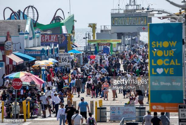 Visitors stroll along the Santa Monica Pier on Monday, April 5, 2021 as Los Angeles County entered the less strict orange tier allowing more places...