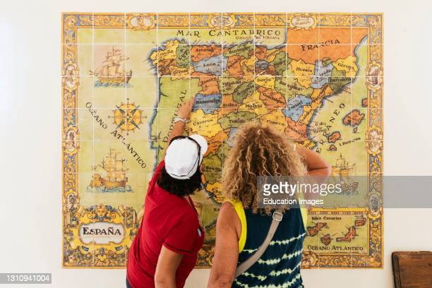 Visitors studying ceramic tiled map of Spain showing provinces, oceans and neighboring countries, ticket and information office of the Alcazar,...