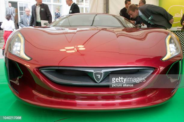 Visitors take a look at the 'Rimac Concept One' electro sportscar at the eMobility Summit on Electromobility at the 'Tagesspiegel' headquarters...