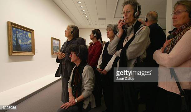 Visitors take a look at works by Vincent van Gogh including 'Starry Night' at the MoMA exhibit on March 24 2004 in Berlin Germany The exhibit which...