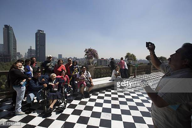 Visitors take a photograph from the balcony of the Chapultepec Castle which houses Mexico's National Museum of History as the Torre Mayor left and...