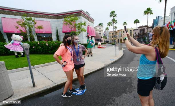 Visitors take a picture at Universal Studios theme park on the first day of reopening from the coronavirus pandemic on June 05 2020 in Orlando Florida