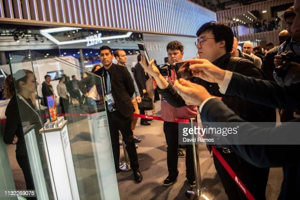 Visitors take a picture to new Huawei Mate X at the Huawei booth on day 2 of the GSMA Mobile World Congress 2019 on February 26 2019 in Barcelona...