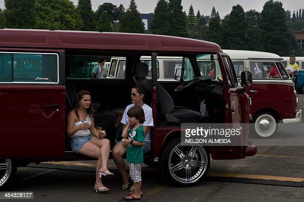 Visitors take a rest in a Kombi during an exhibition at the Volkswagen plant in Sao Bernardo do Campo southern Sao Paulo Brazil on December 8 2013...
