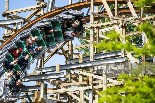 Visitors take a ride on a merry-go-round in the amusement park Walibi Holland in Biddingshuizen, The Netherlands on May 25 as the park reopened after...