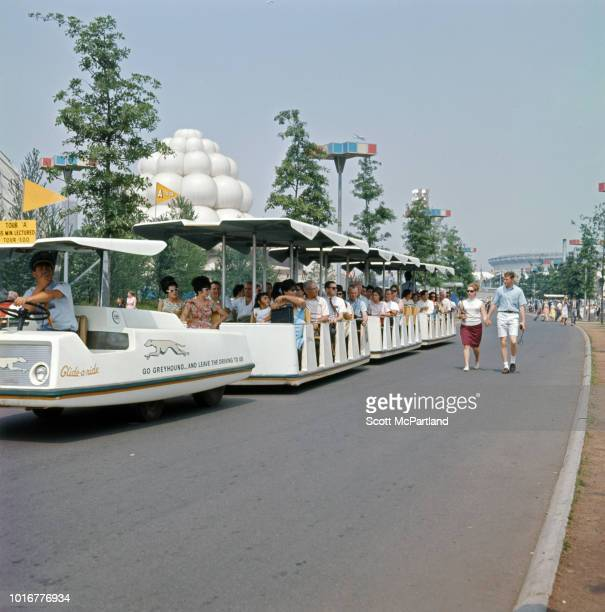 Tourists take a ride on Greyhound's 'Glide O Ride' shuttle bus in Flushing Meadows Park during the World's Fair in Queens New York New York June 1965