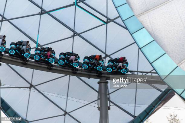 Visitors take a ride on the Tron Lightcyle Power Run rollercoaster at Walt Disney Co's Shanghai Disneyland theme park towards the iconic castle...