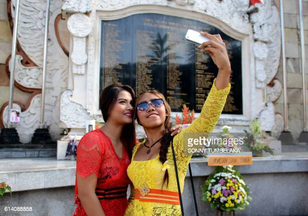 TOPSHOT Visitors take a selfie at the memorial for victims of the 2002 Bali bombings during the 14th anniversary of the blasts in the Kuta tourist...