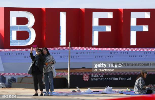 Visitors take a selfie in front of a stage of the BIFF Village a venue of the 22nd Busan International Film Festival at Haeundae beach in Busan on...