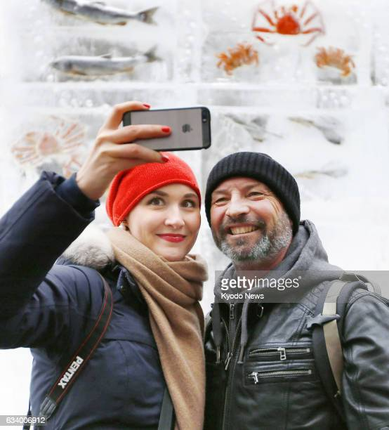 Visitors take a selfie in front of fish frozen in ice blocks at the Sapporo Snow Festival in the Hokkaido city on Feb 6 just months after an...