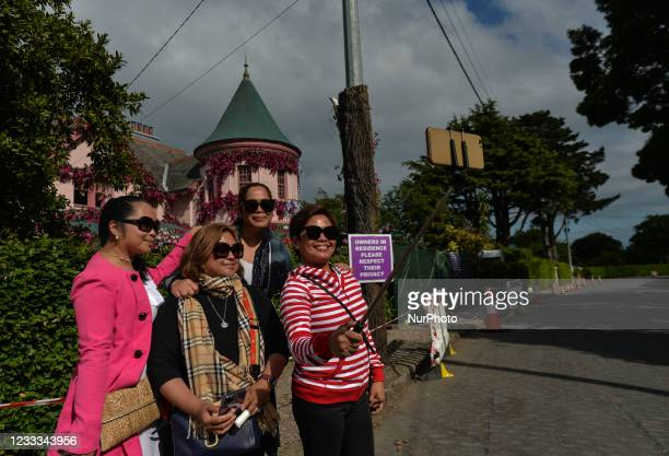 Visitors take a selfie in front of the house in The Burnaby area of Greystones which has been covered from the roof down by stretched pink flowers...