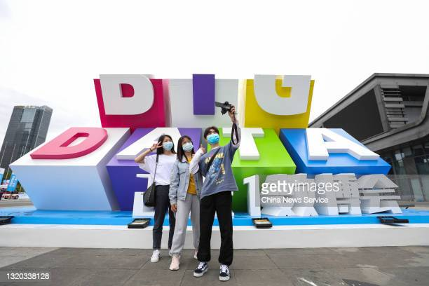 Visitors take a selfie in front of the logo during the China International Big Data Industry Expo 2021 outside Guiyang International Conference and...