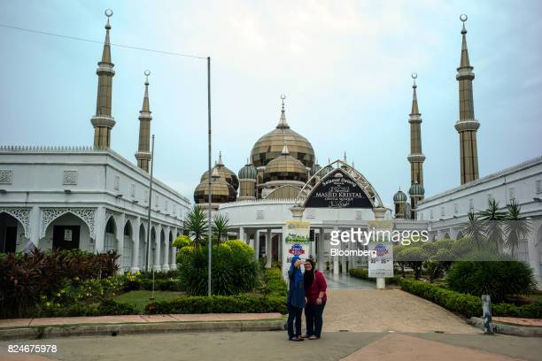 Visitors take a selfie photograph in front of the Crystal Mosque in Kuala Terengganu Terengganu Malaysia on Monday July 23 2017 With a federal...