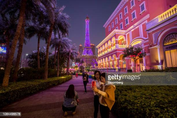 Visitors take a selfie photograph near the Eiffel Tower attraction at the Parisian Macao casino resort operated by Sands China Ltd a unit of Las...