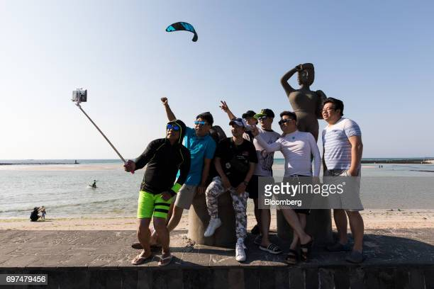 Visitors take a selfie photograph using a monopod at the Geumneung Euddeum Beach in Jeju South Korea on Wednesday June 14 2017 The election ofMoon...
