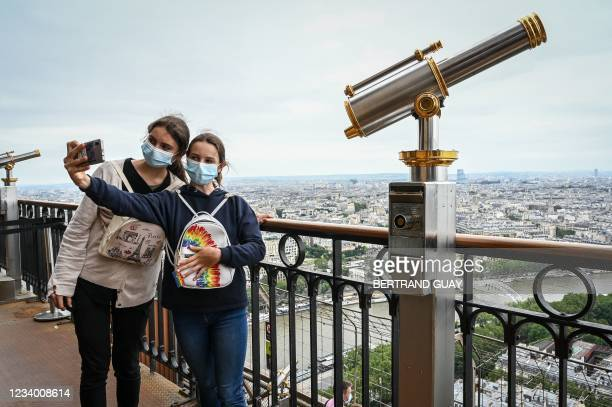 Visitors take a selfie picture as they visit the Eiffel Tower in Paris, on July 16, 2021. - The Eiffel Tower reopened to visitors on July 16 after...