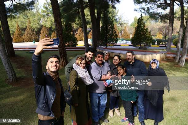 Visitors take a selfie with a caretaker of Gaziantep Zoo Nedim Aslan and the newborn baby chimpanzee named 'Can' as its mom refused to have him at...