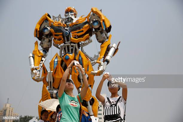 Visitors take a selfie with tenmeter high model of Bumblebee from 'Transformers' at the China Millennium Monument located on the extension line of...