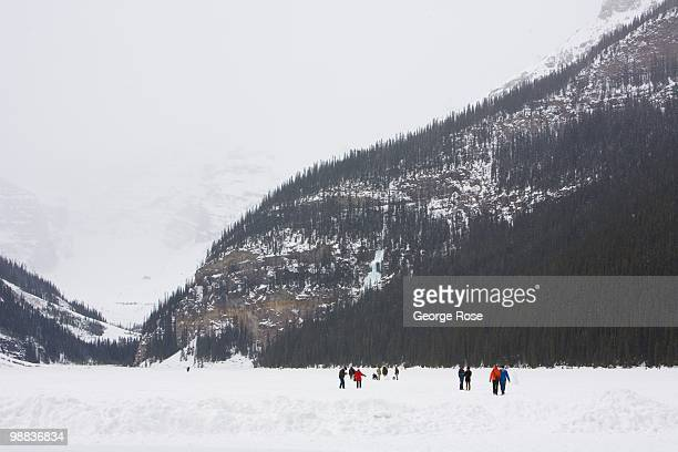 Visitors take a walk on a frozen Lake Louise as seen in this 2010 Lake Louise Canada late morning photo The resort was hit by a late spring snowstorm