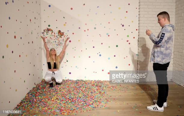 """Visitors take and pose for """"selfie"""" photographs at The Selfie Factory in Westfield London shopping centre in west London on September 11, 2019. -..."""