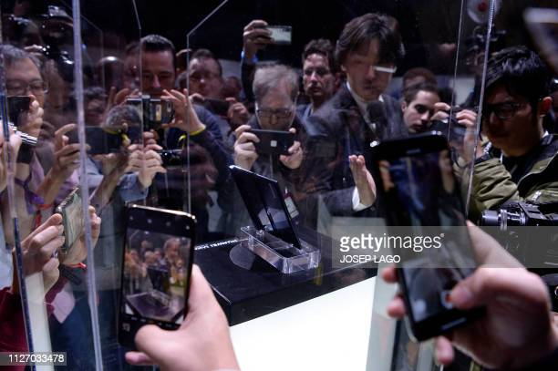 Visitors take images of Huawei's new foldable 5G smartphone HUAWEI Mate X at the Mobile World Congress on the eve of the world's biggest mobile fair...