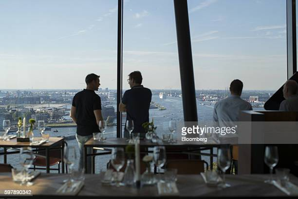 Visitors take in the view of the IJ river and city skyline from a restaurant inside the A'DAM Tower skyscraper in the Noord district of Amsterdam...