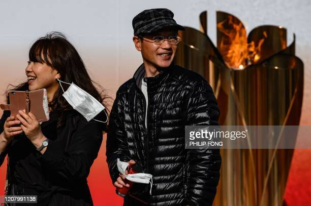 Visitors take off their face masks as they take pictures in front of the Tokyo 2020 Olympic flame on display in Ofunato Iwate prefecture on March 23...